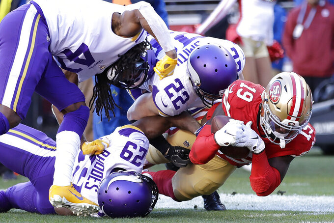 San Francisco 49ers wide receiver Deebo Samuel (19) is tackled by Minnesota Vikings cornerback Xavier Rhodes (29) and free safety Harrison Smith (22) during the first half of an NFL divisional playoff football game, Saturday, Jan. 11, 2020, in Santa Clara, Calif. (AP Photo/Ben Margot)