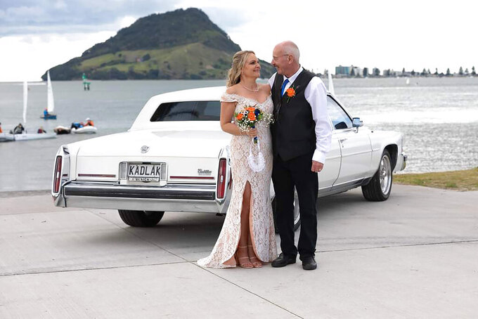 In this photo released by Debra McLean, McLean is pictured with her late husband Phil on their wedding day on Aug. 8, 2020 in Tauranga, New Zealand. Phil was buried in a a giant cream donut coffin, designed by his cousin Ross Hall, who runs a business in New Zealand called Dying Art, which makes colorful custom coffins. (Patrina Davis via AP)