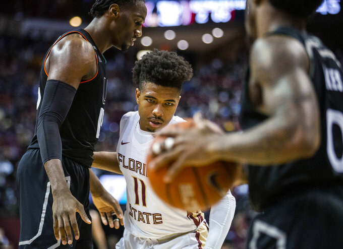 Florida State guard David Nichols keeps his eyes on the ball controlled by Miami guard Chris Lykes, while Nichols moves past Zach Johnson, left, during the second half of an NCAA college basketball game in Tallahassee, Fla., Wednesday, Jan. 9, 2019. Florida State won 68-62. (AP Photo/Mark Wallheiser)