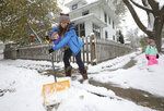 Stephanie Rytilahti shovels the sidewalk with her 1-year-old son, Orion, and 3-year-old daughter, Sorrel, at right, outside their East Side home during a snowfall in Madison, Wis., Thursday, Oct. 31, 2019. (Amber Arnold/Wisconsin State Journal via AP)