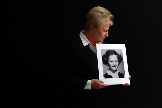 "In this Nov. 20, 2019, photo, Nancy Holling-Lonnecker, 71, poses with a picture taken of her as a young girl, at her home in San Diego. Holling-Lonnecker plans to take advantage of an upcoming three-year window in California that allows people to make claims of sexual abuse no matter how old. Her claim dates back to the 1950s when she says a priest repeatedly raped her in a confession booth beginning when she was 7 years old. ""The survivors coming forward now have been holding on to this horrific experience all of their lives,"" she said. (AP Photo/Gregory Bull)"