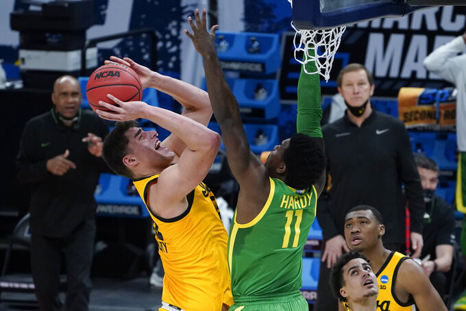 Iowa center Luka Garza (55) shoots on Oregon guard Amauri Hardy (11) during the first half of a men's college basketball game in the second round of the NCAA tournament at Bankers Life Fieldhouse in Indianapolis, Monday, March 22, 2021. (AP Photo/Paul Sancya)