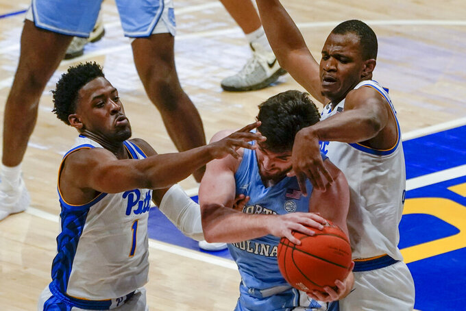 Pittsburgh's Xavier Johnson (1) and Abdoul Karim Coulibaly, right, defend as North Carolina's Walker Kessler looks to pass during the first half of an NCAA college basketball game Tuesday, Jan. 26, 2021, in Pittsburgh. (AP Photo/Keith Srakocic)