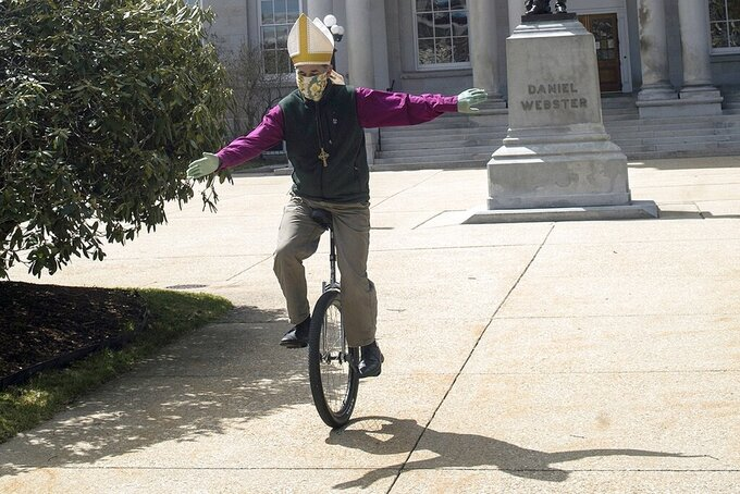 In this April 15, 2020, photo, Bishop of the Episcopal Church of New Hampshire, the Rt. Rev. Robert Hirschfeld, wears his bishop's mitre and mask as he rides outside the State House in Concord, N.H., to raise awareness to keep reducing infection rate and to raise funds for a local charity. (Geoff Forester/Concord Monitor via AP)/The Concord Monitor via AP)