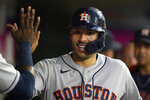 Houston Astros' Carlos Correa is greeted in the dugout after scoring on a two-run home run by Kyle Tucker during the second inning of a baseball game against the Los Angeles Angels Tuesday, Sept. 21, 2021, in Anaheim, Calif. (AP Photo/Marcio Jose Sanchez)
