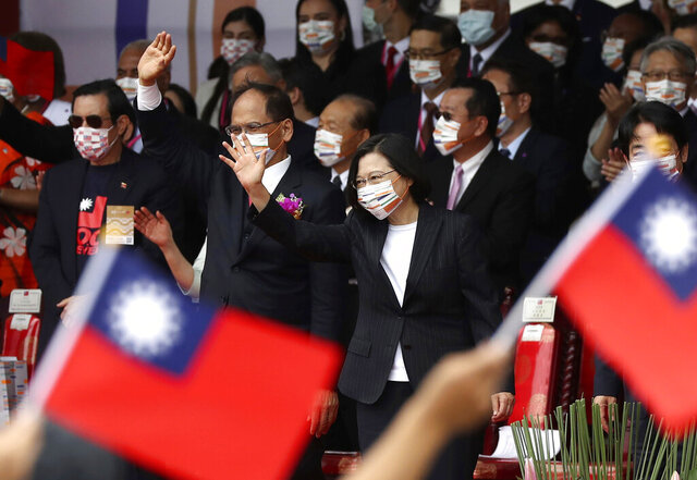 Taiwan's President Tsai Ing-wen, right, and Yu Shyi-kun, speaker of the Legislative Yuan, cheer with audience during National Day celebrations in front of the Presidential Building in Taipei, Taiwan, Saturday, Oct. 10, 2020. President Tsai said Saturday she has hopes for less tensions with China and in the region if Beijing will listen to Taipei's concerns, alter its approach and restart dialogue with the self-ruled island democracy.  (AP Photo/Chiang Ying-ying)