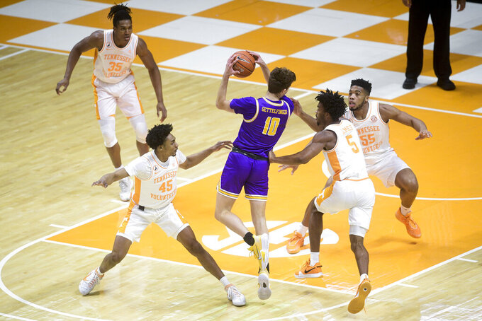 Tennessee Tech's CJ Gettelfinger (10) is defended by Tennessee's Keon Johnson (45), Josiah-Jordan James (5), and E.J. Anosike (55), during an NCAA college basketball game Friday, Dec. 18, 2020, in Knoxville, Tenn. (Caitie McMekin/Knoxville News Sentinel via AP, Pool)
