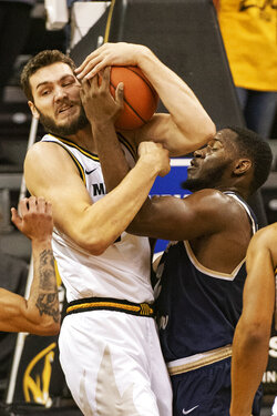 Missouri's Reed Nikko, left, pulls a rebound away from Charleston Southern's Ty Jones, right, during the first half of an NCAA college basketball game Tuesday, Dec. 3, 2019, in Columbia, Mo. (AP Photo/L.G. Patterson)