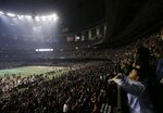 FILE - In this Sunday, Feb. 3, 2013, file photo, fans and members of the Baltimore Ravens and the San Francisco 49ers wait for power to return in the Superdome during an outage in the second half of the NFL Super Bowl XLVII football game in New Orleans. (AP Photo/Gerald Herbert, File)