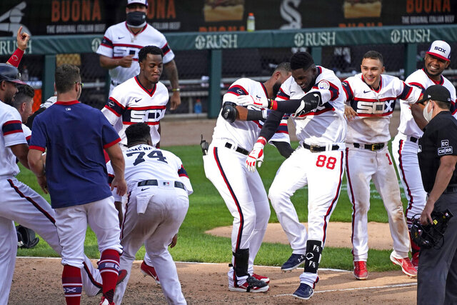 Chicago White Sox's Luis Robert (88) celebrates with teammates after hitting a winning three-run home run against the Kansas City Royals during the 10th inning of a baseball game in Chicago, Sunday, Aug. 30, 2020. (AP Photo/Nam Y. Huh)
