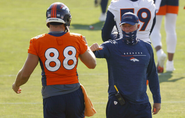 Denver Broncos tight end Nick Vannett, left, greets offensive coordinator Pat Shurmur at the team's NFL football training camp Friday, Aug. 14, 2020, in Englewood, Colo. (AP Photo/David Zalubowski)