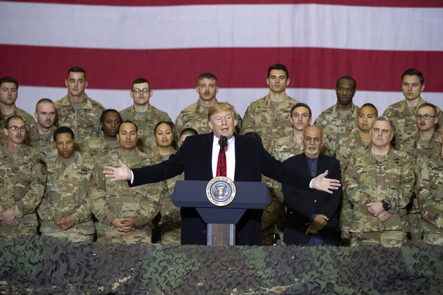 "FILE - In this Nov. 28, 2019 file photo, President Donald Trump, center, with Afghan President Ashraf Ghani and Joint Chiefs Chairman Gen. Mark Milley, behind him at right, addresses members of the military during a surprise Thanksgiving Day visit at Bagram Air Field, Afghanistan. During his election campaign four years ago, Trump vowed to bring all troops home from ""endless wars."