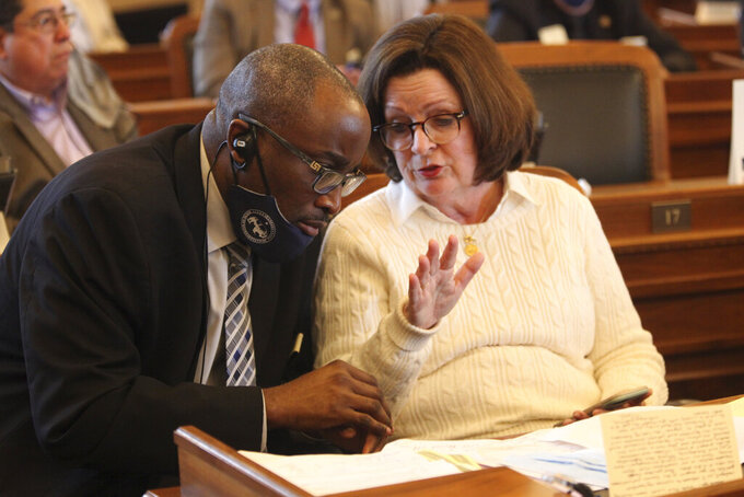 Kansas state Reps. K.C. Ohaebosim, left, D-Wichita, and Kathy Wolfe Moore, D-Kansas City, confer during a House debate over budget legislation, Friday, May 7, 2021, at the Statehouse in Topeka, Kan. Most Democrats voted for the legislation, which helps complete a $21 billion budget for the state fiscal year beginning July 1, 2021. (AP Photo/John Hanna)