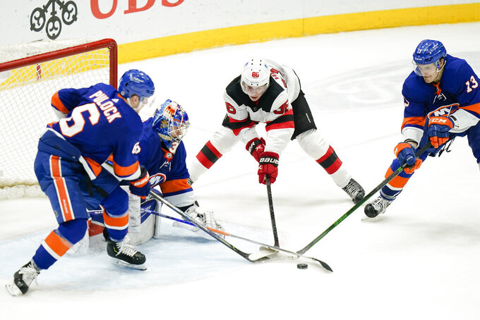 New York Islanders' Ryan Pulock (6) Mathew Barzal (13) and goaltender Ilya Sorokin (30) defend the net from New Jersey Devils' Jack Hughes (86) during the third period of an NHL hockey game Saturday, May 8, 2021, in Uniondale, N.Y. The Islanders won 5-1. (AP Photo/Frank Franklin II)