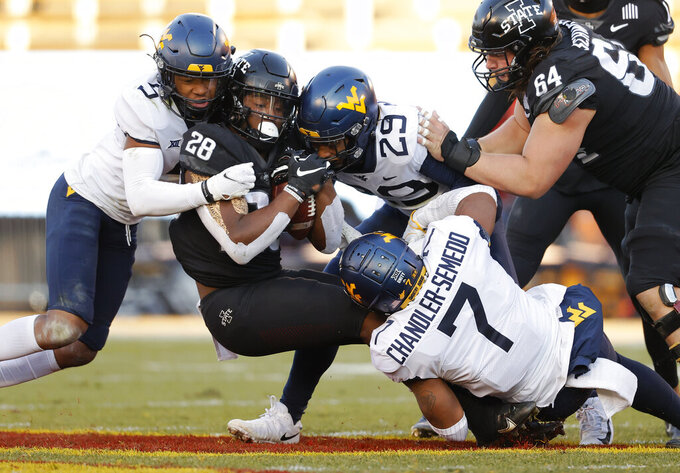 FILE - West Virginia linebacker Josh Chandler-Semedo and teammates cornerback Dreshun Miller, left, and safety Sean Mahone, right, tackle Iowa State running back Breece Hall, center, during the first half of an NCAA college football game in Ames, Iowa, in this Saturday, Dec. 5, 2020, file photo. Chandler-Semedo is part of the All-Bowl Team for picking off a pass, forcing a fumble and delivering 13 tackles in West Virginia's 24-21 victory over Army. (AP Photo/Matthew Putney, File)
