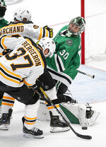 Boston Bruins forwards Brad Marchand (63) and Patrice Bergeron (37) work against Dallas Stars goaltender Ben Bishop (30) for the puck during the first period of an NHL hockey game Thursday, Oct. 3, 2019, in Dallas. (AP Photo/Brandon Wade)