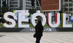 A woman films with her smartphone near the display of South Korea's capital Seoul logo, in Seoul, South Korea, Thursday, July 12, 2018. South Korea's central bank has cut its forecast on the country's economy, citing mounting uncertainties from the U.S.-China trade battle. (AP Photo/Lee Jin-man)