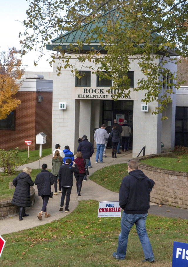 FILE - In this Nov. 3, 2020, file photo, voters wait in line to vote at Wallingford's District 9 at Rock Hill School in Wallingford, Conn. On Wednesday, Nov. 25, 2020, state officials in Connecticut said that a record 1.86 million Connecticut residents voted in the Nov. 3 election, a turnout of nearly 80% of registered voters despite concerns about the coronavirus pandemic. (Aaron Flaum/Record-Journal via AP, File)