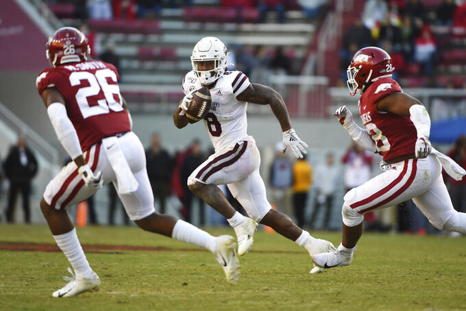 Mississippi State running back Kylin Hill (8) tries to get past Arkansas defenders Micahh Smith (26) and Andrew Parker (28) as he runs for a gain during the second half of an NCAA college football game, Saturday, Nov. 2, 2019 in Fayetteville, Ark. (AP Photo/Michael Woods)