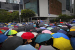 Protesters with umbrellas gather near the Legislative Council as they continuing protest against the unpopular extradition bill in Hong Kong, Monday, June 17, 2019. A member of Hong Kong's Executive Council says the city's leader plans to apologize again over her handling of a highly unpopular extradition bill. (AP Photo/Kin Cheung)