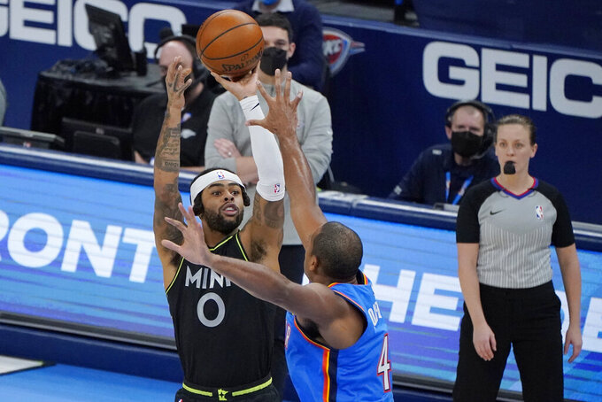 Minnesota Timberwolves guard D'Angelo Russell (0) shoots over Oklahoma City Thunder center Al Horford (42) in the second half of an NBA basketball game Friday, Feb. 5, 2021, in Oklahoma City. (AP Photo/Sue Ogrocki)
