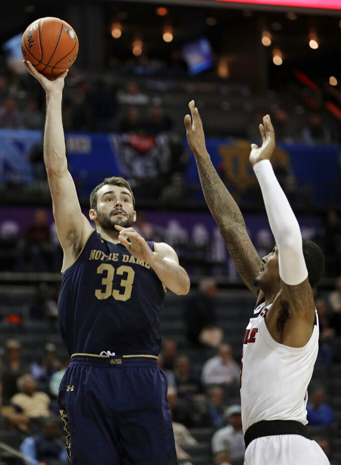 FILE - In this March 13, 2019, file photo, Notre Dame's John Mooney (33) shoots over Louisville's Malik Williams (5) during the second half of an NCAA college basketball game in the Atlantic Coast Conference tournament in Charlotte, N.C. Mooney averaged team highs of 14.1 points and 11.2 rebounds for the injury-plagued Irish last season. (AP Photo/Nell Redmond, File)