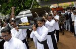 Clergymen carry coffins for burial during a funeral service for Easter Sunday bomb blast victims at St. Sebastian Church in Negombo, Sri Lanka, Tuesday, April 23, 2019. (AP Photo/Gemunu Amarasinghe)