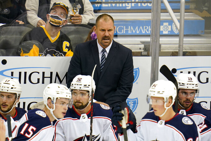 Columbus Blue Jackets head coach Brad Larsen stands behind his bench during the first period of an NHL exhibition hockey game against the Pittsburgh Penguins in Pittsburgh, Monday, Sept. 27, 2021. (AP Photo/Gene J. Puskar)