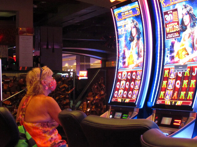 A woman plays a slot machine at the Golden Nugget casino in Atlantic City N.J. on July 2, 2020. Figures released Monday, Aug. 24, 2020, by New Jersey gambling regulators show Atlantic City's casinos lost $112 million in the second quarter of 2020 when all nine casinos were closed due to the coronavirus outbreak, compared to a profit of nearly $160 million in the second quarter of 2019. (AP Photo/Wayne Parry)