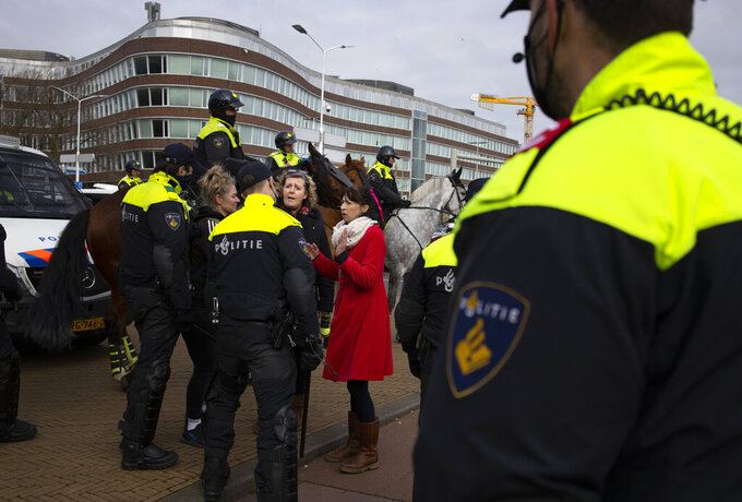 Two women argue with the police during a demonstration ahead of three days of voting starting Monday in a general election, to protest government policies including the curfew, lockdown and coronavirus related restrictions in The Hague, Netherlands, Sunday, March 14, 2021. (AP Photo/Peter Dejong)