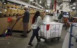 Postal workers wear masks and gloves during the coronavirus pandemic as they physically distance from each other at the United States Postal Service processing and distribution center on Thursday, April 30, 2020, in Oakland, Calif. (AP Photo/Ben Margot)