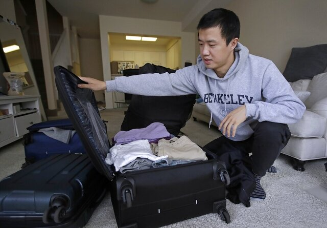 FILE - In this Feb. 4, 2019, photo, Leo Wang packs a suitcase at his home in San Jose, Calif. Wang has found himself trapped in an obstacle course regarding H-1B work visas for foreigners. His visa denied and his days in the United States numbered,  A federal judge on Thursday, Oct. 1, 2020, temporarily lifted a visa ban on a large number of work permits, undercutting a measure that the Trump administration says will protect American jobs in a pandemic-wracked economy. (AP Photo/Ben Margot, File)