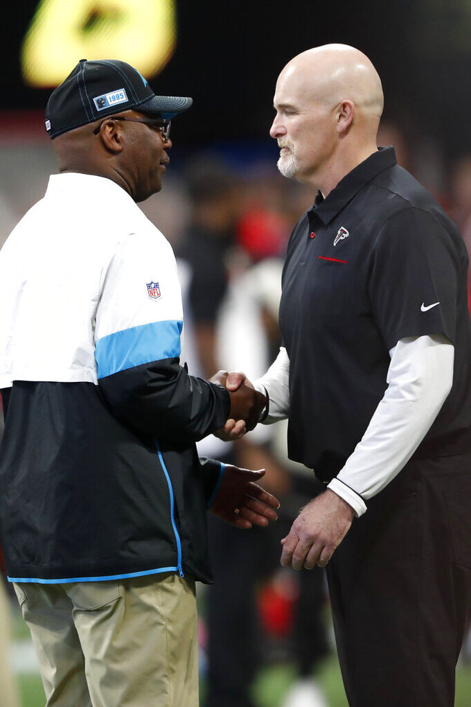 Carolina Panthers interim head coach Perry Fewell, left, speaks with Atlanta Falcons head coach Dan Quinn before the first half of an NFL football game, Sunday, Dec. 8, 2019, in Atlanta. (AP Photo/John Bazemore)