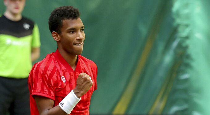 Canada's Felix Auger-Aliassime celebrates winning his ATP Tour Singles, Men, Round of 16 tennis match against  Switzerland's Roger Federer in Halle, Germany, Wednesday, June 16, 2021. (Friso Gentsch/dpa via AP)