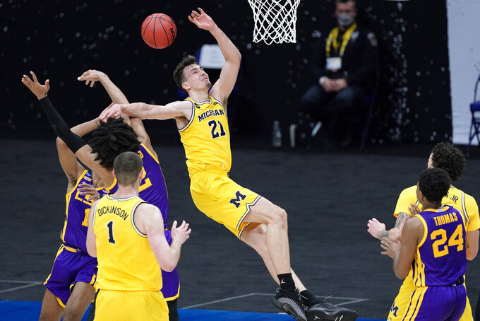Michigan guard Franz Wagner (21) loses control of the ball as he drives to the basket during the first half of a second-round game against LSU in the NCAA men's college basketball tournament at Lucas Oil Stadium Monday, March 22, 2021, in Indianapolis. (AP Photo/AJ Mast)