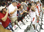 In this Dec. 9, 2018, photo, Alabama guard Kira Lewis Jr. (2) slaps hand with fans, including Luke Ratliff, second from left, after Alabama defeated Arizona in NCAA college basketball game at Coleman Coliseum in Tuscaloosa, Ala Health officials in Indiana said Saturday, April 3, they are investigating whether anyone was exposed to COVID-19 by Alabama residents following Friday night's death of Ratliff, who was in Indianapolis for the NCAA Tournament last weekend. Ratliff, a 23-year-old Alabama student, died after a brief illness, his father, Bryan Ratliff, told The Tuscaloosa News. The newspaper, citing multiple sources it did not identify, reported Ratliff died of complications related to COVID-19. (Gary Cosby Jr./The Tuscaloosa News via AP)