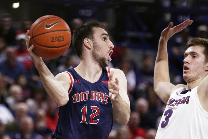 Saint Mary's guard Tommy Kuhse (12) passes the ball while pressured by Gonzaga forward Filip Petrusev (3) during the first half of an NCAA college basketball game in Spokane, Wash., Saturday, Feb. 29, 2020. (AP Photo/Young Kwak)