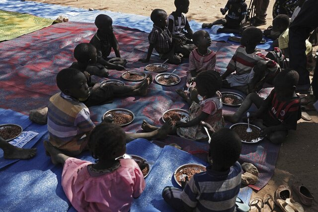 Children eat food distributed during a visit organized by The World Food Program (WFP) at Koge school, in the conflict-affected remote town of Kauda, Nuba Mountains, Sudan, Jan. 9, 2020. Sudanese Prime Minister Abdalla Hamdok, accompanied by United Nations officials, embarked on a peace mission Thursday to Kauda, a rebel stronghold, in a major step toward government efforts to end the country's long-running civil conflicts. (AP Photo/Nariman El-Mofty)