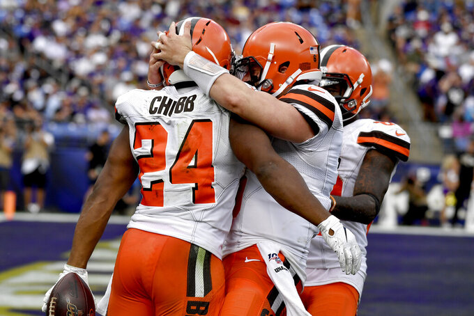 Cleveland Browns running back Nick Chubb (24) is hugged by quarterback Baker Mayfield (6) and wide receiver Jarvis Landry after scoring on a touchdown run against the Baltimore Ravens during the second half of an NFL football game Sunday, Sept. 29, 2019, in Baltimore. (AP Photo/Brien Aho)