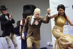 Edson Mambinge, centre, is accompanied on stage after winning the Mr Albinism Zimbabwe 2019 at an albino pageant held in Harare, early Saturday, May 25, 2019. About 70,000 of Zimbabwe's estimated 16 million people are born with albinism, according to government figures. They often stand out, making them a subject at times of discrimination, ridicule and dangerously misguided beliefs. The Mr. and Miss Albinism Zimbabwe competition, now in its second year, is a chance to push back. (AP Photo/Tsvangirayi Mukwazhi)