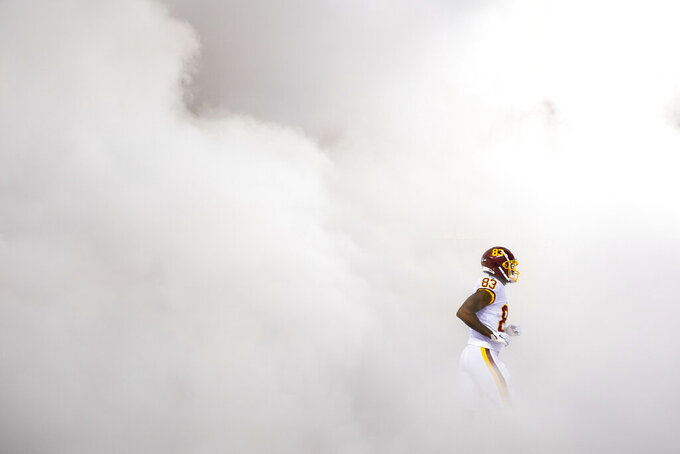 Washington Football Team tight end Ricky Seals-Jones (83) runs through a cloud of smoke as he takes the field during team introductions before the start of first half of an NFL football game against the New York Giants, Thursday, Sept. 16, 2021, in Landover, Md. (AP Photo/Patrick Semansky)