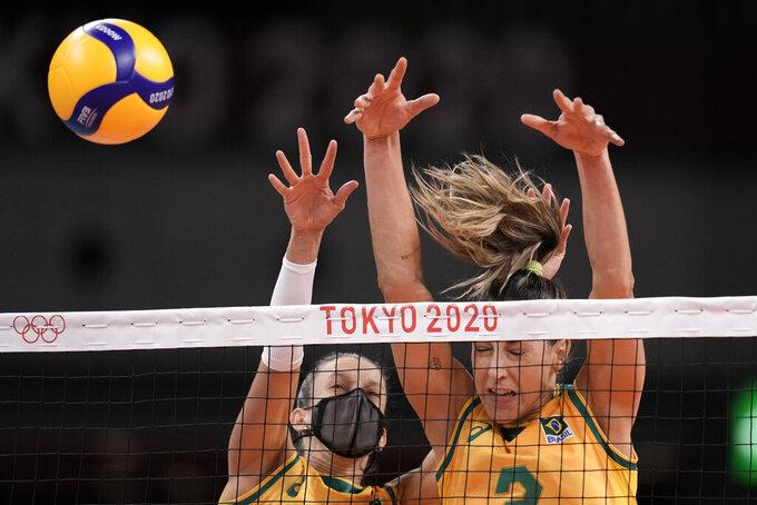 Brazil's Macris Fernanda Silva Carneiro and Caroline de Oliveira Saad Gattaz block at the net during a women's volleyball preliminary round pool A match against South Korea, at the 2020 Summer Olympics, Sunday, July 25, 2021, in Tokyo, Japan. (AP Photo/Manu Fernandez)