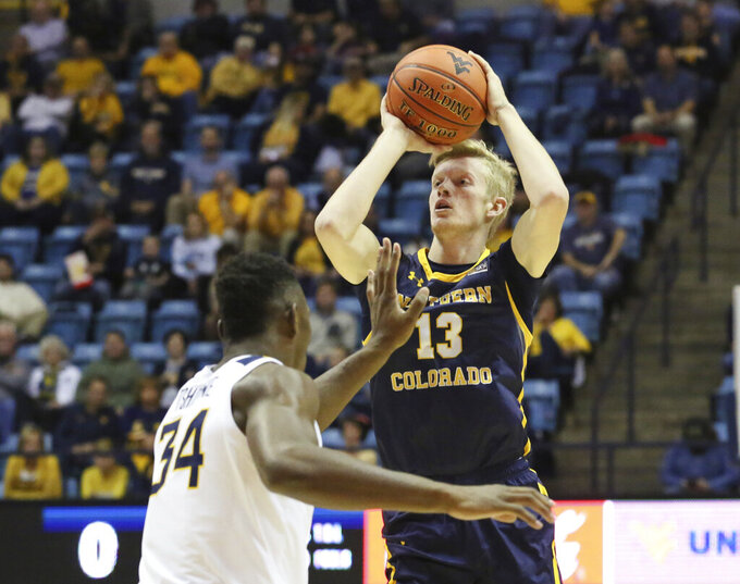 Northern Colorado's Bodie Hume (13) is defended by West Virginia's Oscar Tshiebwe (34) as he goes to make a shot during the first half of an NCAA college basketball game Monday Nov. 18, 2019, Morgantown, W.Va. (AP Photo/Kathleen Batten)
