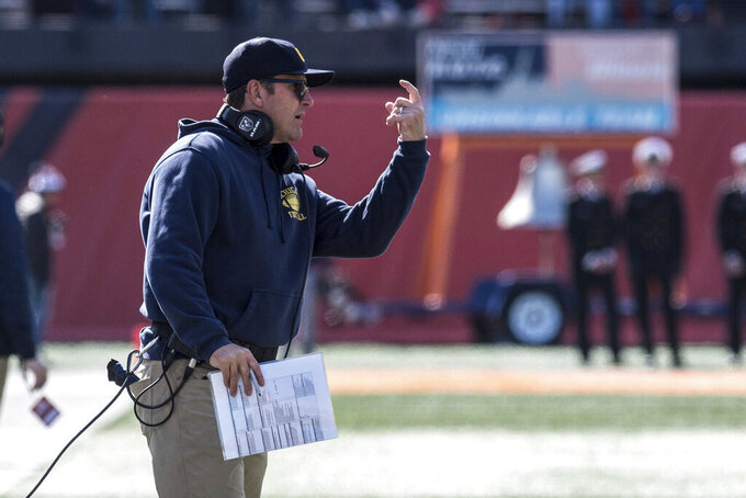 Michigan head coach Jim Harbaugh gestures in the first half of an NCAA college football game against Illinois, Saturday, Oct. 12, 2019, in Champaign, Ill. (AP Photo/Holly Hart)
