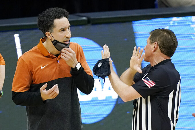 Texas head coach Shaka Smart, left, talks with an official during the first half of a college basketball game between Texas and Abilene Christian in the first round of the NCAA tournament at Lucas Oil Stadium in Indianapolis Saturday, March 20, 2021. (AP Photo/Mark Humphrey)