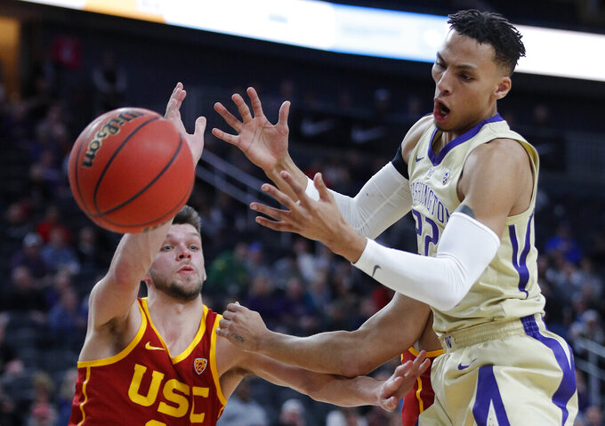Southern California's Nick Rakocevic, left, and Washington's Dominic Green battle for the ball during the first half of an NCAA college basketball game in the quarterfinal round of the Pac-12 conference tournament Thursday, March 14, 2019, in Las Vegas. (AP Photo/John Locher)