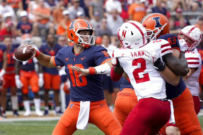 Illinois quarterback Brandon Peters passes under pressure from Nebraska linebacker Caleb Tannor during the first half of an NCAA college football game against the Nebraska Saturday, Aug. 28, 2021, in Champaign , Ill. (AP Photo/Charles Rex Arbogast)