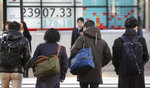 People walk by an electronic stock board of a securities firm in Tokyo, Tuesday, Jan. 21, 2020. Asian stock markets have tumbled as concern about the impact of a Chinese disease outbreak on tourism and regional economies grows. (AP Photo/Koji Sasahara)