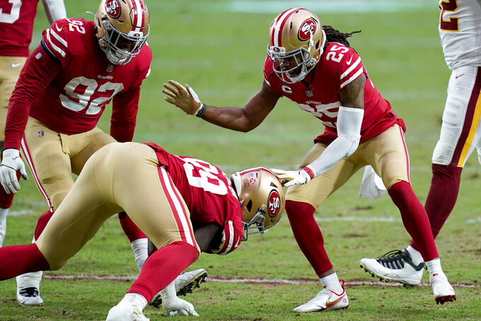 San Francisco 49ers cornerback Richard Sherman (25), defensive end Kerry Hyder (92) and defensive tackle Javon Kinlaw (99) celebrates a defensive stop against the Washington Football Team during the first half of an NFL football game, Sunday, Dec. 13, 2020, in Glendale, Ariz. (AP Photo/Ross D. Franklin)