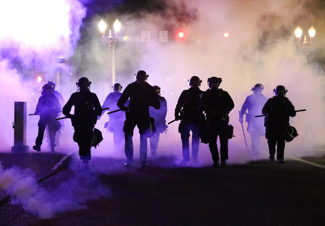 Police officers walk enveloped by teargas in Portland, Friday, March 29, 2020.  After hours of largely peaceful demonstrations, violence escalated late Friday in downtown Portland, as hundreds of people gathered to protest the Minneapolis police killing of a black man, George Floyd . (Dave Killen/The Oregonian via AP)